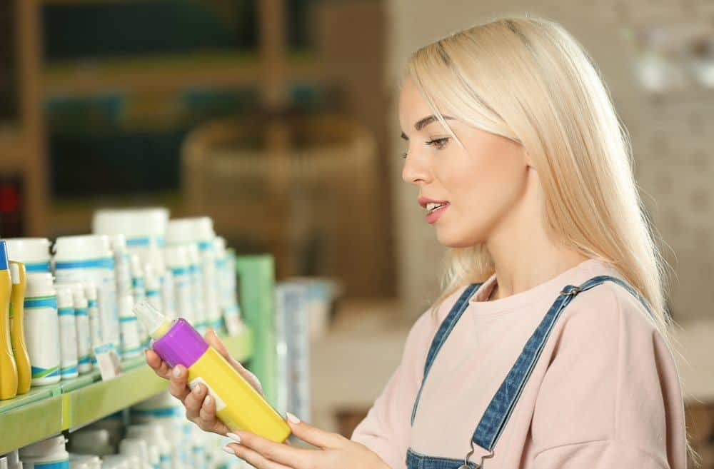 Woman selecting animal shampoo in pet shop